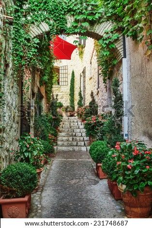 Narrow street with flowers in the old town  in France. - stock photo