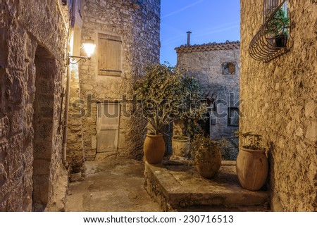 Narrow street with flowers in the old village Peille in France. Night view - stock photo
