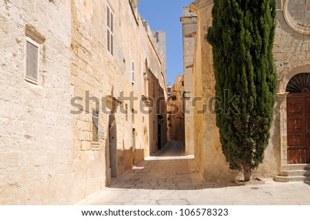 Narrow Street with little Chapel and Cypress Tree in the historic site of Mdina (The city of Silence) on Malta. - stock photo