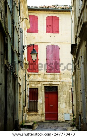 Narrow the street in Arles (Provence, France). Weathered stucco walls, red wooden shutters and forging lanterns.  - stock photo