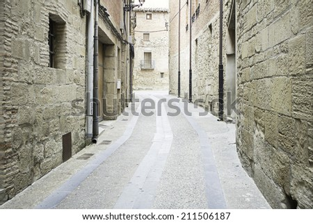 Narrow village street with houses, construction - stock photo