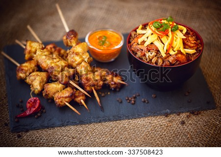 Nasi goreng and chicken skewers, indonesian food - stock photo