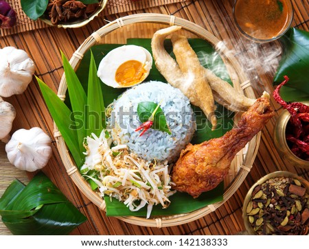 Nasi kerabu is a type of nasi ulam, popular Malay rice dish. Blue color of rice resulting from the petals of  butterfly-pea flowers. Traditional Malaysian food, Asian cuisine. - stock photo