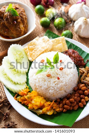 Nasi lemak traditional malaysian spicy rice dish, fresh cooked with hot steam. Served with belacan, ikan bilis, acar, peanuts and cucumber. Decoration setup. - stock photo