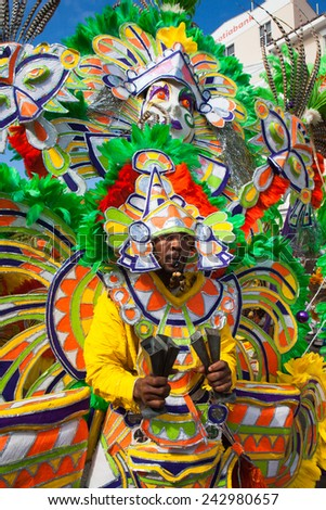 NASSAU, THE BAHAMAS - JANUARY 1 - Whistle blowing dancer dressed in bright orange and green feathers, performs in Junkanoo, a traditional island cultural festival in Nassau, Jan 1, 2011 - stock photo