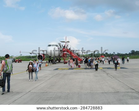 NATHON SI THAMMARAT, THAILAND - OCTOBER 18, 2013: Aircraft and passengers on airfield of airport. - stock photo