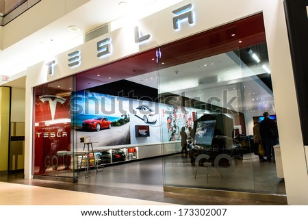 NATICK - JANUARY 25, 2014: Exterior view of a Tesla motors store in the mall on January 25, 2013 in Natick, USA. Tesla Motors produced the Tesla Roadster, the first fully electric sports car. - stock photo