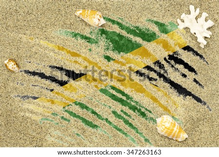 National country flag of Jamaica under a beach background with sand, sea shells and coral - stock photo