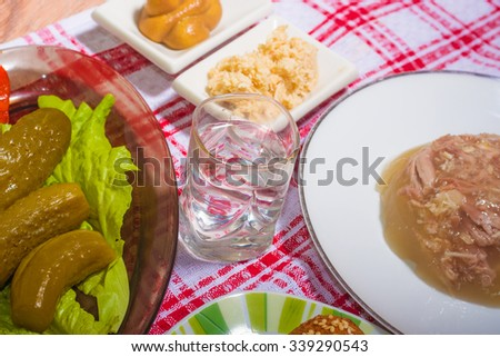 national dish: meat jelly with potatoes,salty cucumbers and russian vodka - stock photo