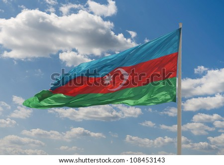 National flag of Azerbaijan against blue sky - stock photo
