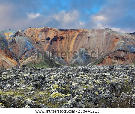 National Park Landmannalaugar in Iceland. Pieces of gray and black lava, sometimes covered with green moss. In the background -  orange and blue rhyolite mountains - stock photo