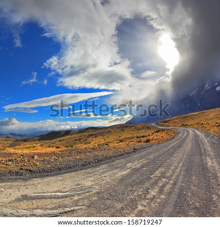 National Park Torres del Paine in Chile. Awesome cloud over a gravel road. The picture was taken Fisheye lens - stock photo