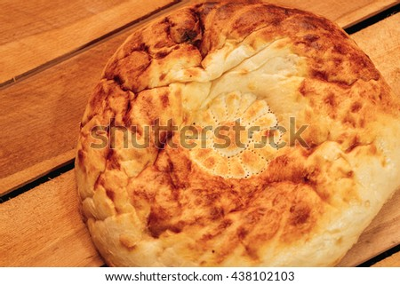National Uzbek bread on a wooden background, top view. - stock photo