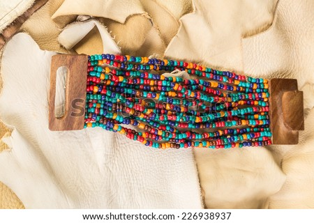 Native American Beaded Bracelet with wooden clasp against scraps of buckskin and rawhide. - stock photo