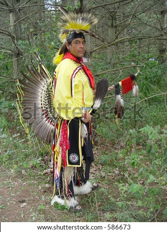 Native American man holding eagle feathers. - stock photo