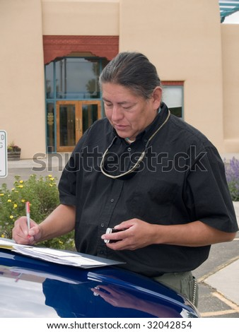 Native American man writing notes on the hood of his car. - stock photo