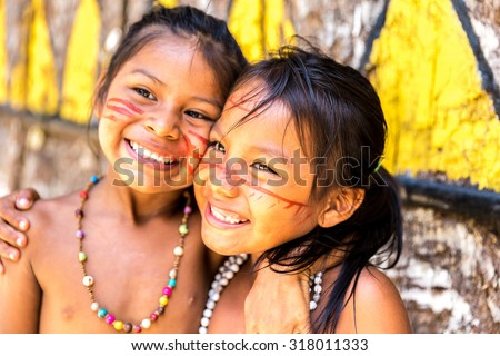 Native Brazilian girls smiling at an indigenous tribe in the Amazon - stock photo