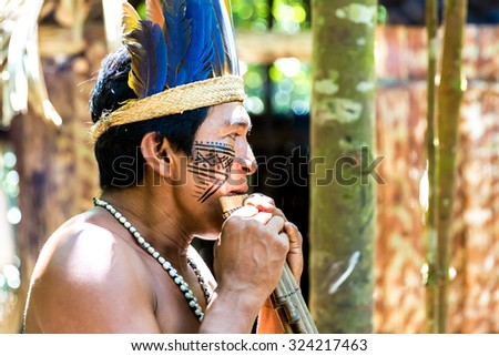 Native Brazilian man playing wooden flute at an indigenous tribe in the Amazon - stock photo
