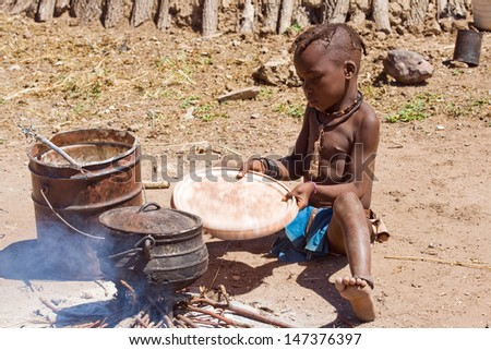 Native Himba boy cooking lunch, Namibia - stock photo