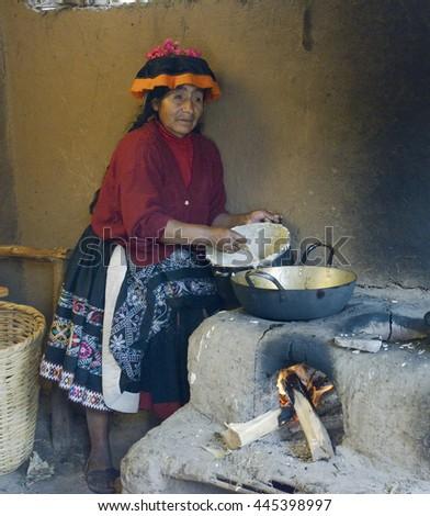 Native Peruvian woman preparing Cachangas aka fried bread on a primitive stone oven. October 22, 2012 - Paru Paru, Peru - stock photo
