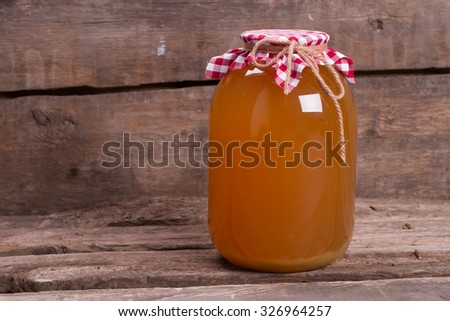 Natural apple juice on wooden boards. Ecoproduct on an old wooden shelf. Canning juice in the cellar. - stock photo