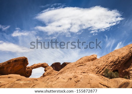 Natural arch and white cloud, Valley of Fire State Park, Nevada, USA - stock photo