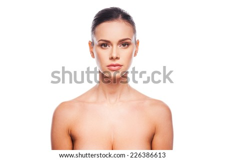 Natural as she is. Portrait of beautiful young shirtless woman looking at camera while standing against white background - stock photo