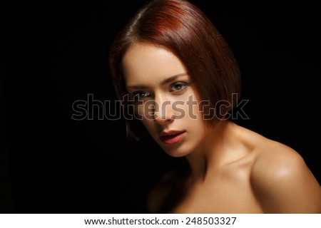 Natural as she is. Portrait of beautiful young shirtless woman looking down while standing isolated against black background - stock photo