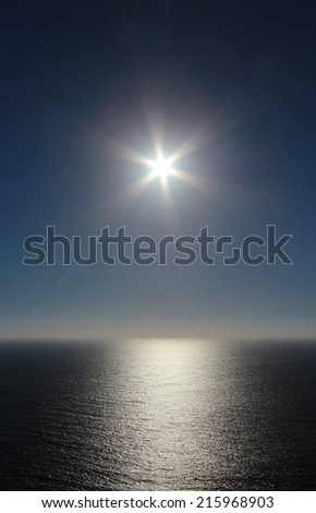 Natural background of sun on blue sky over sea - stock photo