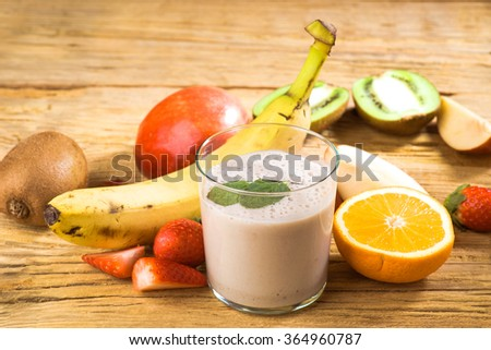 Natural banana smoothie surrounded by fruit on wooden base - stock photo