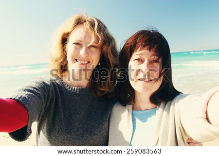 Natural beautiful women smiling on the beach with the sand, sea and blue sky in the background. Selfie - stock photo