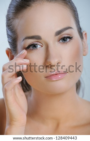 Natural beauty girl closeup gently touch the skin around the eyes - stock photo