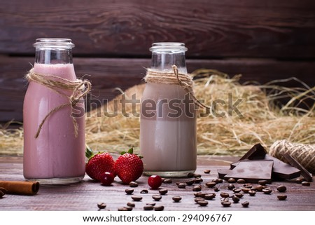Natural chocolate and strawberry milkshakes on a wooden background. - stock photo