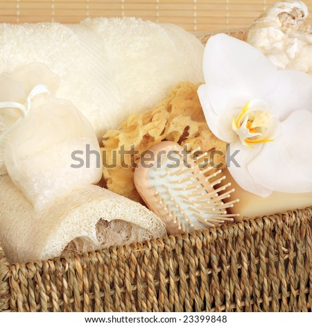 Natural cleansing products in a wicker basket including a cream flannel, soap, sponge, loofah,, hand brush, vanilla bath salts in a net bag and a white orchid  flower. - stock photo