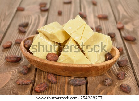 Natural cocoa butter in a wooden bowl on a brown background - stock photo