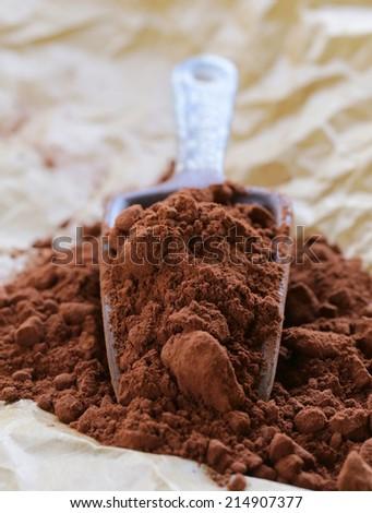 natural cocoa powder (chocolate) in a ceramic scoop - stock photo