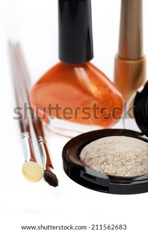 Natural colored modern eye shadow with a sheen for subtly enhancing the beauty of the eye with complimentary colored bronze nail varnish and two applicators on white - stock photo