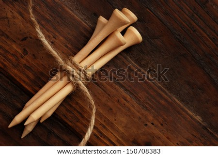 Natural colored wooden golf tees (tied with twine) on rustic, dark wood background with copy space.  Low key still life with directional, natural lighting for effect. - stock photo
