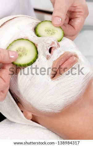 Natural facial treatment, young woman laying with facial mask and cucumber on eyes. - stock photo