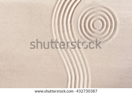 Natural flowing wave form and concentric circles raked in the smooth sand in a Japanese Zen Garden portraying tranquility and meditation in a wellness concept - stock photo