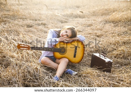 Natural food backdrop Copy space for inscription Horizontal Country latin hispanic girl playing guitar in autumn reap wheat field Cute hippie woman sit on warm summer land and dream about something - stock photo
