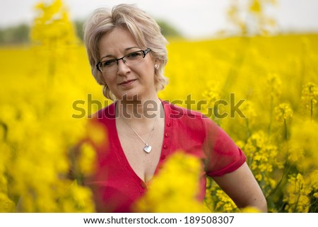 Natural forty years old woman outdoors at rape field - stock photo