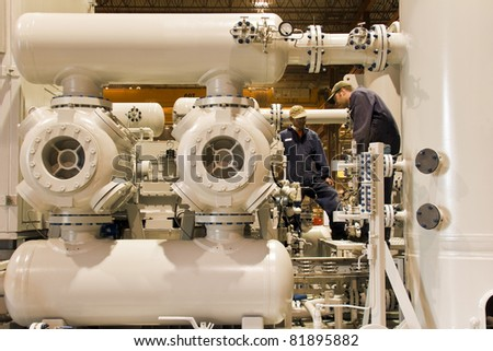Natural gas compressor station  with two working technicians - stock photo