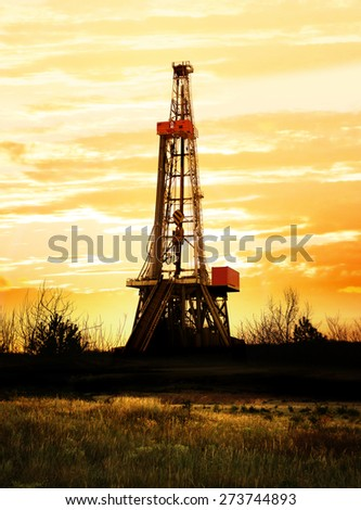 Natural gas production, land drilling rig at sunset. - stock photo
