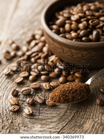 Natural ground coffee heap in bowl on coffee grains background - stock photo