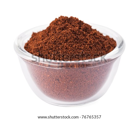 Natural ground coffee heap in transparent glass bowl, isolated on white - stock photo