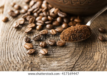 Natural ground coffee heap in transparent glass bowl on Coffee grains background. - stock photo
