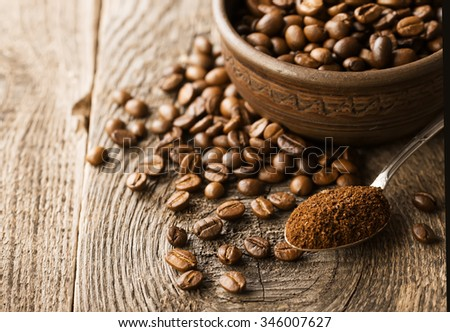 Natural ground coffee heap in transparent glass bowl on �offee grains background - stock photo