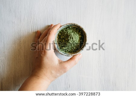natural hair dye in a ceramic bowl, ceramic bowl with a green pigment, basma green on a white background, green pigment. - stock photo