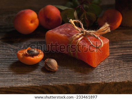 Natural handmade soap with scrub from apricot pits to care for face and body, spa, aromatherapy. On a wooden surface. still life - stock photo